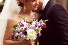Härliga brud- par som har gyckel i parkera på deras bukett för blomma för bröllopdag Arkivbilder