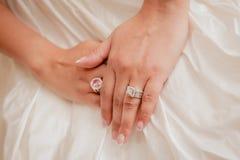 Härliga brud- vigselringar planlägger Smyckat med ett handlag av den vita härliga bröllopsklänningdesignen arkivfoton