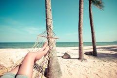 Härliga brunbrända ben av sexiga kvinnor koppla av på hängmattan på den sandiga tropiska stranden Arkivbild