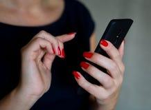 Härliga brunn-ansade kvinnliga fingrar rymmer en mobiltelefon arkivfoto
