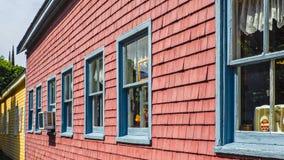 Härliga byggnader med blåa fönster på den färgrika väggen i prinsen Edward Island, Kanada royaltyfria foton