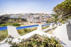 Härliga Carvoeiro med färgrika hus vid den breda sandiga stranden arkivbilder