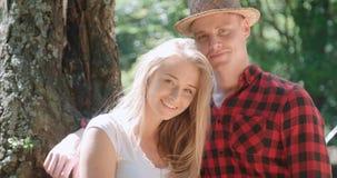 Härliga caucasian par som kopplar av i en skog under solig dag Royaltyfri Foto
