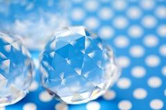 Härliga crystal ädelstenar på blå vit prickbakgrund Abstrakta diamantstenar, geometriska polygonformer Moget frö av granatäpplet Arkivfoto