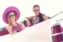 Härliga damer med solexponeringsglas som rider en retro bil för tappning Arkivfoton