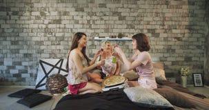 Härliga damer som tycker om tiden i sovrummet som kommer med pizza och tillsammans spenderar en vänlig tid, är de stock video