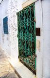 Härliga dekorativa fönster på den vita väggen som är typisk för Tunisien/traditionellt gammalt grönt fönster med det dekorativa s Arkivfoton