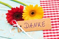 Härliga det gerberablommor och kortet med det tyska ordet, Danke, hjälpmedel tackar dig Royaltyfri Fotografi