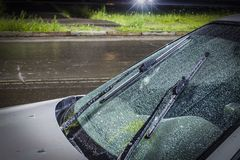 härliga droppar av vatten på vindrutan av bilen med exponeringsglasrengöringsmedlen vände på, under en åskväder och ett regn i arkivbilder