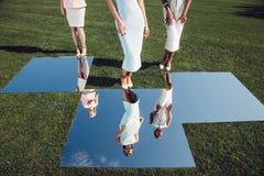 Härliga eleganta flickor som poserar på golfbana med grönt gräs och speglar fotografering för bildbyråer