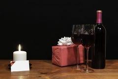 Härliga etsade vinexponeringsglas och flaskan av rött vin, den vita stearinljuset, slogg in närvarande med pilbågen på trätabelle royaltyfri foto