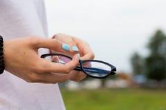Härliga exponeringsglas för exponeringsglas på bakgrunden av naturen i händerna av en härlig flicka fotografering för bildbyråer