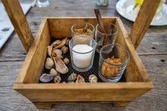 Härliga exponeringsglas och skeden för socker för innehav för tappningträaskkorg för kaffe och te med havet beskjuter garnering p Arkivbild