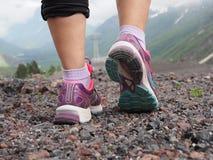 Härliga färgrika kvinnors skor för Saucony spring, gymnastikskor till kvinnors den bakre sikten för ben med berg i bakgrunden Con arkivfoton