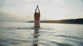 Härliga flickakörningar på vattnet Spridd sprej Den spensliga unga kvinnan kör i aftonen på solnedgången stock video