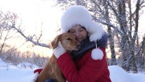 Härliga flickaleenden, smeker hennes älskade hund i vinter parkerar in flickan med en jaga hund går i vinter i skog arkivfoto