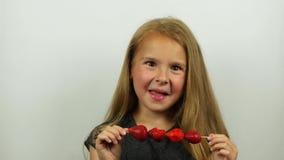 Härliga flickasmakjordgubbar på steknålar Le flickan äter en jordgubbe som slickar kanter lager videofilmer
