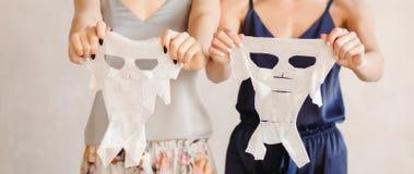 Härliga flickor använder omsorg för hud för föryngringframsidamaskering För behandlingbrunnsort för begrepp ansikts- ark för till fotografering för bildbyråer
