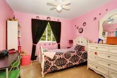 Härliga flickor hyr rum i ljus rosa färgfärg med sniden wood säng Arkivfoton