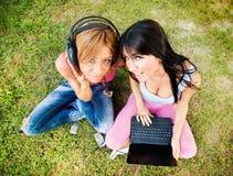 Härliga flickor lyssnar musik Arkivfoto