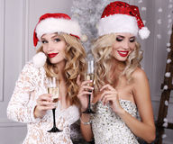 Härliga flickor med blont hår som poserar bredvid julgranen royaltyfri foto