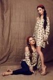 Härliga flickor med mörkt hår i klänningar med tryck av röda vallmo Arkivfoton