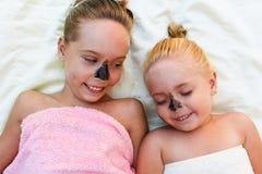Härliga flickor med maskeringen för ansiktsbehandlingsvartlera arkivbild