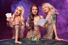 Härliga flickor med perfekta frisyrer och det ljusa sminket poserar anseende på en spela tabell Kasino poker royaltyfri fotografi