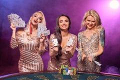 Härliga flickor med perfekta frisyrer och det ljusa sminket poserar anseende på en spela tabell Kasino poker arkivfoton