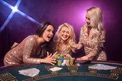 Härliga flickor med perfekta frisyrer och det ljusa sminket poserar anseende på en spela tabell Kasino poker arkivbilder