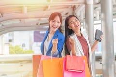 Härliga flickor med shoppingpåsar som går på gallerian Arkivfoton