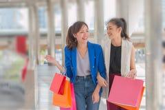 Härliga flickor med shoppingpåsar som går på gallerian Royaltyfria Bilder