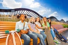 Härliga flickor med skateboarder sitter på bänk Royaltyfri Foto