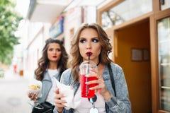 Härliga flickor med smink och frisyren som dricker den mousserande drinken och äter snabbmat arkivbilder