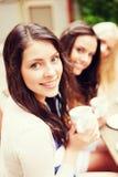 Härliga flickor som dricker kaffe i kafé Arkivbild