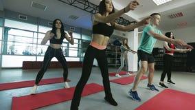 Härliga flickor som gör övningar med instruktören i konditionidrottshallen arkivfilmer