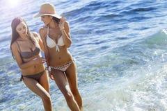 Härliga flickor som tycker om sommar och havsvatten arkivfoto