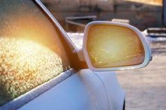 Härliga frostiga modeller i backspegeln på exponeringsglaset av bilen och ilskna blicken av solen arkivfoton