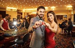 Härliga glamourpar mot bakgrunden av kasinopokerrouletten arkivfoton