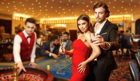 Härliga glamourpar mot bakgrunden av kasinopokerrouletten arkivbild