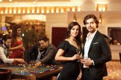 Härliga glamourpar mot bakgrunden av kasinopokerrouletten arkivfoto