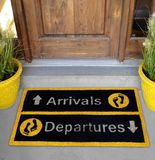 Härliga gula och svarta ankomster och mattt för dörr för avvikelser utomhus- med fotmoment utanför hem med blomkruka 2 fotografering för bildbyråer