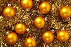 Härliga guld- bollar för jul på guld- bakgrund Royaltyfri Bild