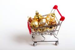 Härliga guld- gåvor med bandet och julbollar i shoppingvagn Arkivbild