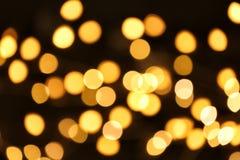 Härliga guld- ljus på mörker Bokeh verkställer arkivfoton