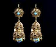 Härliga guldprydnader på en mörk bakgrund Smycken för kvinnor Halsband och örhängen arkivfoto
