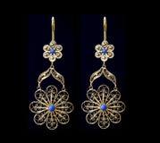 Härliga guldprydnader på en mörk bakgrund Smycken för kvinnor Halsband och örhängen royaltyfri fotografi