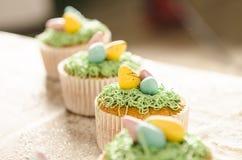 Härliga gulliga påskmuffin med påskgarneringar Arkivbilder