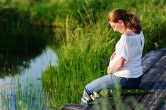 härliga händer över gravid tummykvinna Royaltyfria Bilder