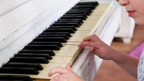 Härliga händer av flickan som spelar det vita pianot 4k lager videofilmer